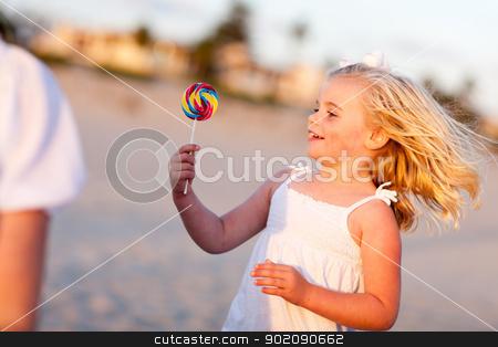 Adorable Little Girl Enjoying Her Lollipop Outside stock photo, Adorable Little Girl Enjoying Her Lollipop Outside at the Beach. by Andy Dean