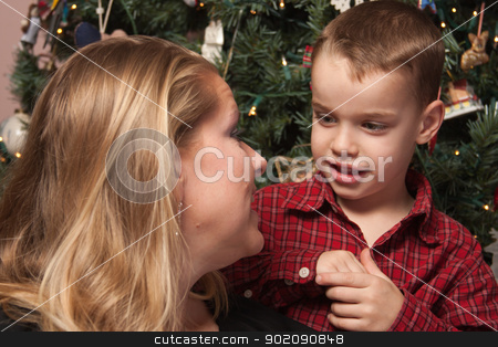 Adorable Son Talking to Mom in Front Of Christmas Tree stock photo, Adorable Son Talking to Mom in Front Of Their Christmas Tree. by Andy Dean