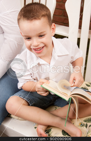 Cute Young Boy Reading His Book stock photo, Cute Young Boy Reading His Book Indoors Next to His Mom. by Andy Dean