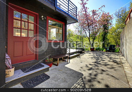 Front red door of black wood house with garden view. stock photo, Front red door of black wood house with garden view during spring. by iriana88w