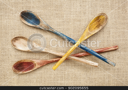 rustic wooden spoons stock photo, rustic wooden painted spoons on burlap canvas by Marek Uliasz