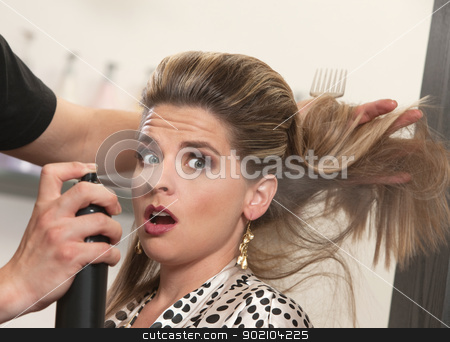 Stylist Uses Hairspray on Surprised Woman stock photo, Pretty woman is startled by stylist using hair spray by Scott Griessel