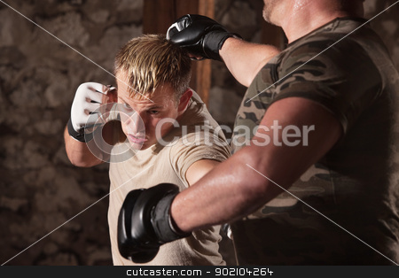 MMA Fighter Dodges a Punch stock photo, Blond MMA fighter dodges a punch and hits opponent by Scott Griessel