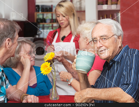 Man in Cafe with Friends stock photo, Mature man drinking coffee while friends order at cafe by Scott Griessel