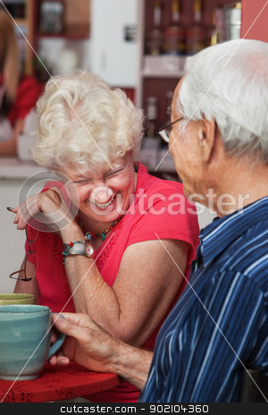 Laughing Mature Woman stock photo, Older Caucasian woman laughing at table with man by Scott Griessel