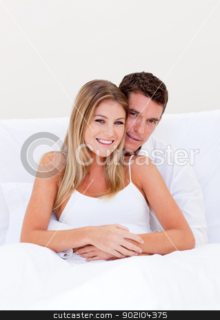 Portrait of an enamored couple sitting on bed  stock photo, Portrait of an enamored couple sitting on bed  at home by Wavebreak Media