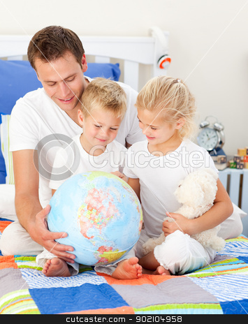 Jolly father and his children holding a terretrial globe  stock photo, Jolly father and his children holding a terretrial globe sitting on a bed by Wavebreak Media
