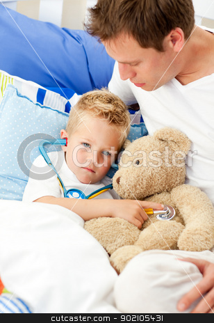 Earing father and his sick son playing with a stethoscope stock photo, Earing father and his sick son playing with a stethoscope sitting on bed by Wavebreak Media