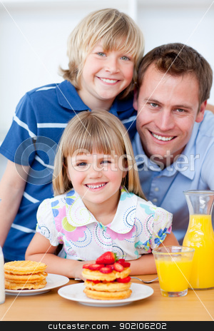 Happy family eating waffles with strawberries stock photo, Happy family eating waffles with strawberries in the kitchen by Wavebreak Media