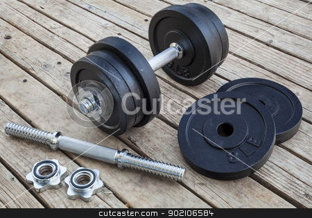 cast iron dumbbell  stock photo, cast iron dumbbell and weight plates on wooden deck - home gym concept by Marek Uliasz