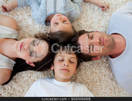 Family sleeping on the floor with heads together stock photo, Young Family sleeping on the floor with heads together by Wavebreak Media