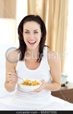 Attractive young woman having breakfast  stock photo, Attractive young woman having breakfast sitting on her bed by Wavebreak Media