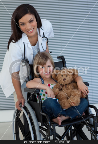 Little girl on a wheelchair holding her teddy bear stock photo, Smiling Little girl on a wheelchair holding her teddy bear by Wavebreak Media