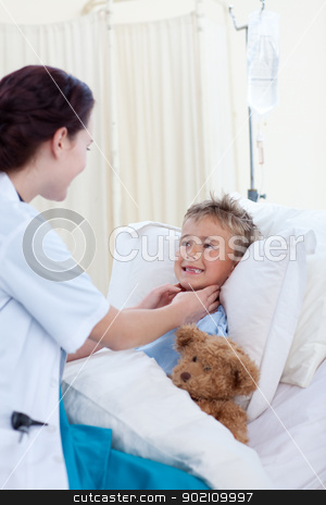 Female doctor checking child throat stock photo, Female doctor checking child throat in bed by Wavebreak Media