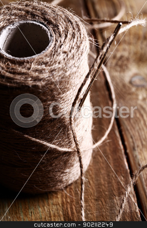 Spool of thread and needle over wooden surface stock photo, Artistic image of spool of thread and needle over wooden surface by yekostock