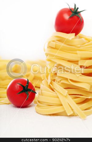 Dry pasta and cherry tomatoes composition stock photo, Dry pasta and cherry tomatoes composition over a white background by yekostock