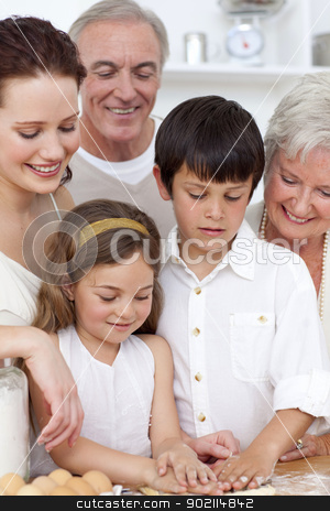 Grandparents looking at children baking in the kitchen stock photo, Grandparents looking at boy and a little girl baking in the kitchen by Wavebreak Media