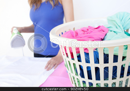 Close-up of a woman ironing  stock photo, Close-up of a woman ironing against a white background by Wavebreak Media