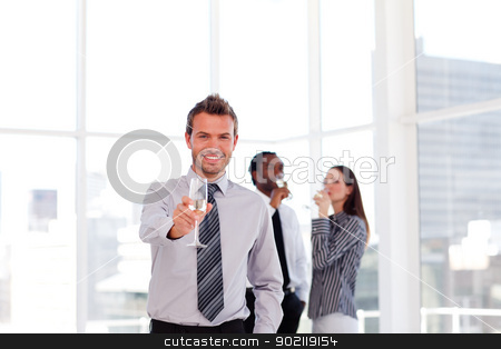 Business people celebrating a success with champagne stock photo, Young business people celebrating a success with champagne in the office by Wavebreak Media