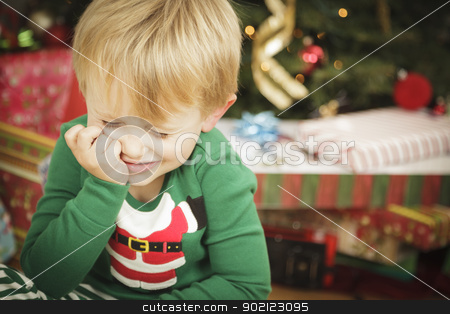 Young Grumpy Boy Sitting Near Christmas Tree stock photo, Grumpy Cute Young Boy on Christmas Morning Near The Tree. by Andy Dean
