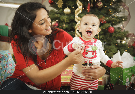 Ethnic Woman With Her Newborn Baby Christmas Portrait stock photo, Young Attractive Ethnic Woman With Her Newborn Baby Near The Christmas Tree. by Andy Dean