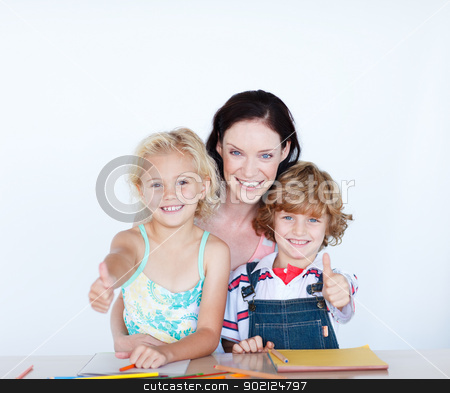 Children doing homework with their mother with thumbs up stock photo, Happy children doing homework with their mother with thumbs up by Wavebreak Media