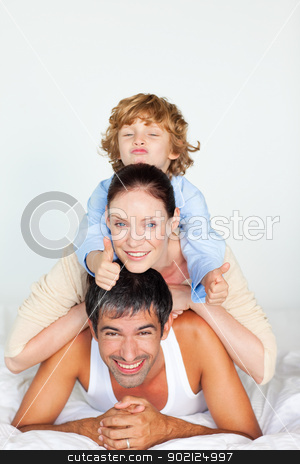 Family playing in bed with thumb up stock photo, Happy family playing in bed with thumb up by Wavebreak Media