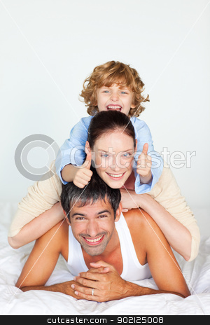 Parents and son playing in bed stock photo, Parents and children playing together in bed by Wavebreak Media