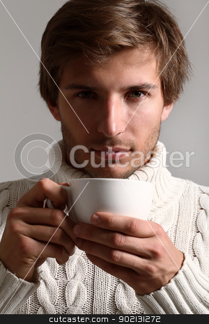 Handsome man in sweater drinking tea stock photo, Handsome and beautiful man in white sweater drinking tea by yekostock