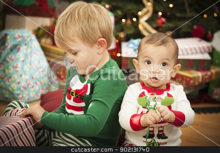 Baby and Young Boy Enjoying Christmas Morning Near The Tree stock photo, Cute Infant Baby and Young Boy Enjoying Christmas Morning Near The Tree. by Andy Dean