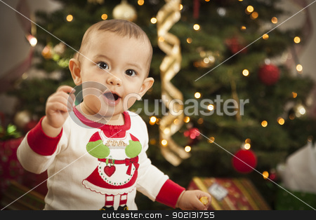 Infant Mixed Race Baby Enjoying Christmas Morning Near The Tree stock photo, Cute Infant Mixed Race Baby Enjoying Christmas Morning Near The Tree. by Andy Dean