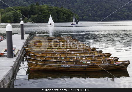 Several moored brown wooden row boats on a lake. stock photo, Several moored brown wooden row boats on a lake. by Wayne Shirt