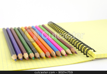 Color pencils on the yellow writing-book stock photo, Color pencils on the yellow writing-book. Shallow DOF. by Sergei Devyatkin