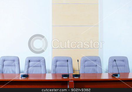 Conference hall with microphones stock photo, before a conference, the microphones in front of empty chairs. by Sergey Nivens