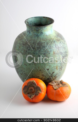 Persimmon with vase stock photo, Persimmons with a green vase on white background. by Henrik Lehnerer