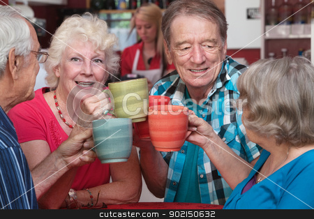 Smiling Woman Toasting with Friends stock photo, Smiling woman with senior friends toasting with coffee mugs by Scott Griessel