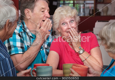 Man and Woman Whispering stock photo, Senior man and woman sharing whispering as friends look on by Scott Griessel