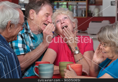 Laughing Elderly Couple with Friends stock photo, European man whispering to laughing senior woman with friends by Scott Griessel