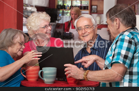 Seniors Having Fun with Computer in Cafe stock photo, Group of four European senior citizens on laptop in cafe by Scott Griessel