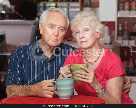 Serious Senior Couple with Coffee stock photo, Serious senior couple at table in restaurant by Scott Griessel