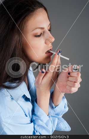 beautiful young brunette woman with cigarette stock photo, Attractive brunette girl with cigarette at grey background by Aikon