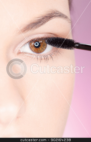 woman applying mascara stock photo, Close up of a woman applying mascara on eye by iMarin