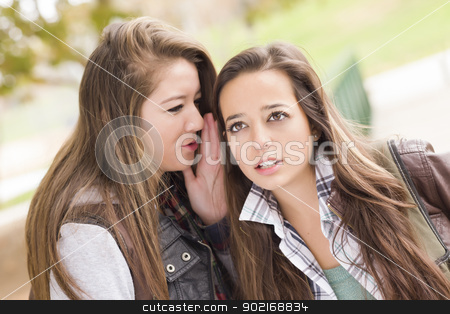 Mixed Race Woman Whispering Secrets Outside stock photo, Two Attractive Mixed Race Woman with Backpacks Whispering Secrets Outside. by Andy Dean