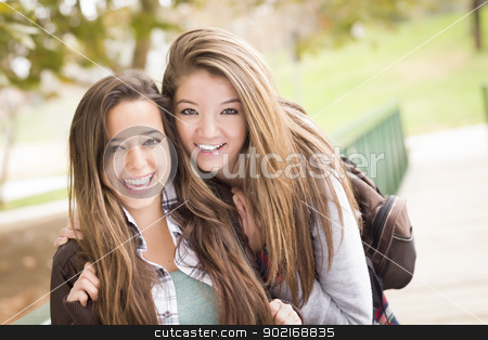 Mixed Race Women Pose for a Portrait Outside stock photo, Two Attractive Mixed Race Women with Backpacks Pose for a Portrait Outside. by Andy Dean