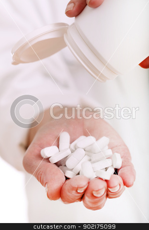 Close up of doc hand holding pills isolated stock photo, Close up of doc hand holding pills isolated on a white by yekostock