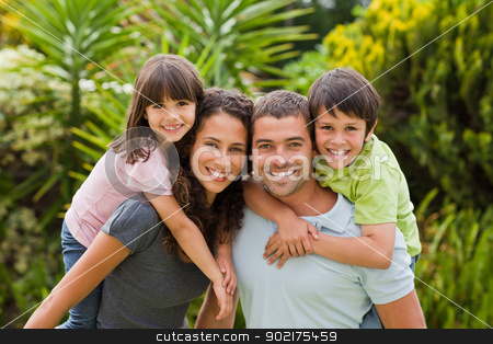 Mother and father giving children a piggyback stock photo, Mother and father giving children a piggyback by Wavebreak Media