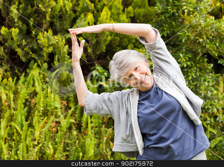 Mature woman doing her streches in the garden stock photo, Mature woman doing her streches in the garden by Wavebreak Media