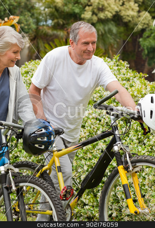 Mature couple walking with their bikes stock photo, Mature couple walking with their bikes by Wavebreak Media