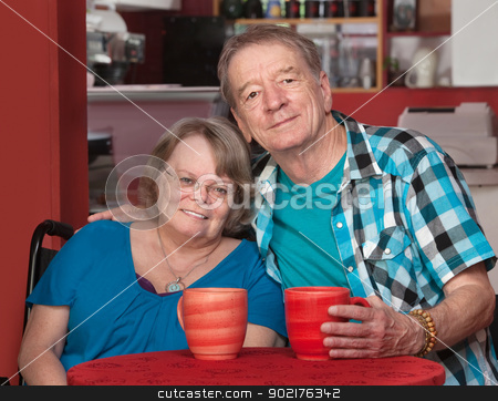 Smiling Senior Male and Female at Table stock photo, Joyful senior friends sitting with mugs at table by Scott Griessel