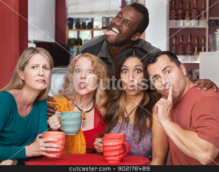Group Making Funny Faces stock photo, Mixed group of friends making faces in a cafe by Scott Griessel